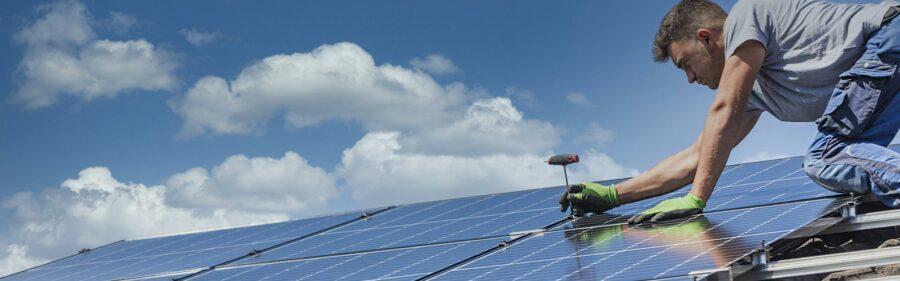 Man installing solar panel on house roof